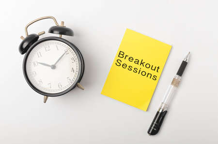 Top view of a alarm clock and pen with written Breakout Sessions on white background. Selective focus.