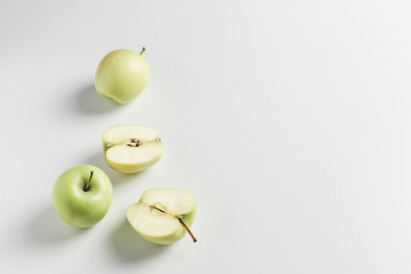 green apples on wooden stand on white background Stock Photo