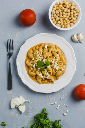 pasta Pipa the rigat with a sauce of chickpeas and tomatoes, sprinkled with feta cheese and cilantro on a white plate on a light grey background high angle