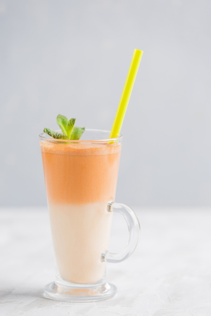 Fresh carrot juice with oat milk and mint. Vegetarian drink for healthy food in a transparent glass on a light background side view. Reklamní fotografie