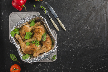 chicken in foil baked in oven with tomatoes, pepper, arugula and green salad on black background top view