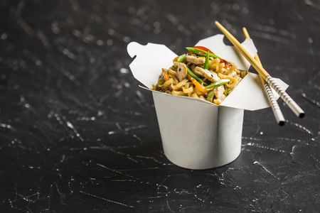 Chinese noodles in a box with chicken and vegetables with sticks. Wok food delivery from restaurant on dark background from side view. Stok Fotoğraf