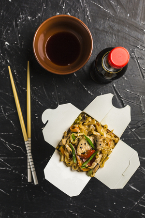 Chinese noodles in a box with chicken and vegetables with sticks. Wok food delivery from restaurant on dark background from top view.