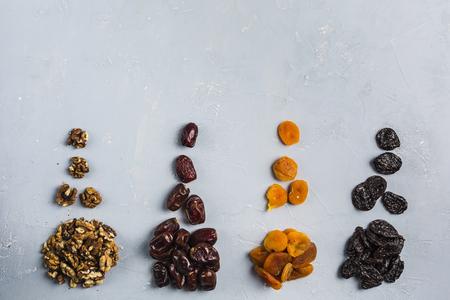 Alimenti di datteri del Ramadan (iftar), noci, albicocche secche, prugne su sfondo azzurro vista dall'alto. Immagine di concetto.