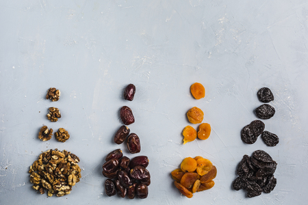 Foods of Ramadan (iftar) dates, nuts, dried apricots, prunes on a light blue background top view. Concept image.
