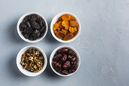 Foods of Ramadan (iftar) dates, nuts, dried apricots, prunes in cups on a light blue background top view. Stock Photo