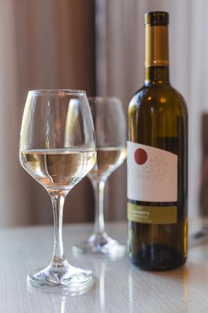 orange wine in glasses and bottle on light background close-up Imagens