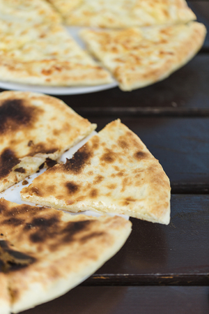 National Georgian dish khachapuri Imereti and megrelian with cheese on a dark wooden background top view.
