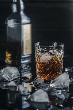 alcoholic whiskey drink in an ice glass with a bottle in the background, on a black background, close-up 写真素材