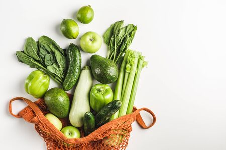 Green vegetables and fruits in orange string bag on white background. Zucchini, cucumber, pepper, avocado, celery, spinach, lime. The view from the top. Isolated from the space mine. No plastic, only natural materials.