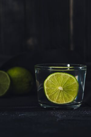 a piece of lime in a glass of water to useful power on a dark background in a low key with copyspace