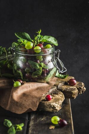 Gooseberries in a transparent jar with mint leaves on a wooden Board shot in low key closeup with copyspace Imagens