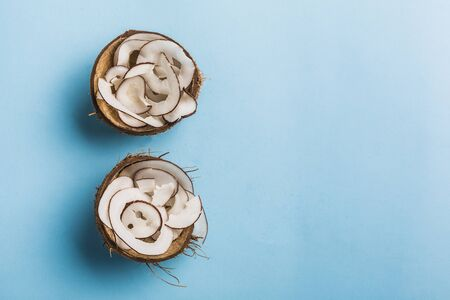 Coconut chips in a bowl of coconut on a blue background, flatlay, a natural product for healthy nutrition. Concept.