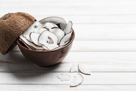 Coconut chips in a brown bowl on a white wooden background, side view close-up, a natural product for healthy nutrition. Фото со стока