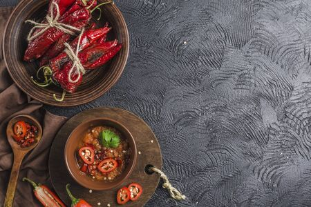 Spicy chili on a dark background in ceramic plates, flatlay. Used as an ingredient for harissa, ajika, muhammara. East and middle East kitchen. Copyspace. Reklamní fotografie