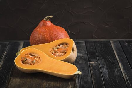 Fresh pumpkin on dark wooden background close up with copy space, vegetables for healthy eating 版權商用圖片