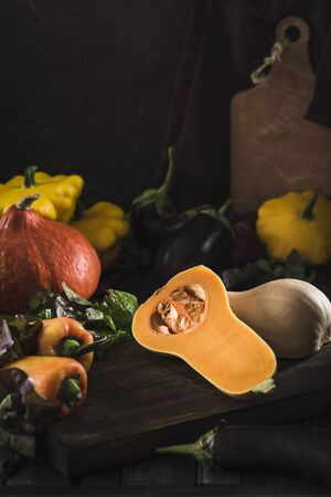 Fresh harvest of vegetables from pumpkin, eggplant, pepper, lettuce, red onion and squash on a dark wooden background close-up with a copy space