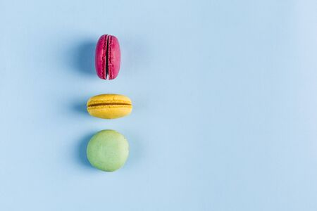 Multicolored macaroons on a blue background, top view, Flatley with copy space. Dessert with melon, lemon and raspberry flavor. Art