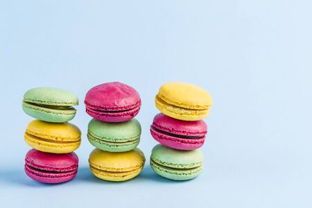 Colorful macaroons on a blue background, close-up, Flatley with copy space. Dessert with melon, lemon and raspberry flavor. Art 版權商用圖片