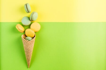 Multicolored macaroons in a waffle cone on a green and yellow background, top view, Flatley with copy space. Dessert with melon, lemon and raspberry flavor. Art