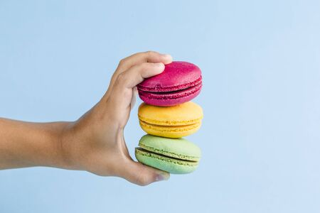 Colorful macaroons in a childs hand on a blue background, close-up, Flatley with copy space. Dessert with melon, lemon and raspberry flavor. Art