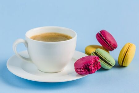 Colorful macaroons with a white Cup of coffee on a blue background, close-up, Flatley with copy space. Dessert with melon, lemon and raspberry flavor. Art