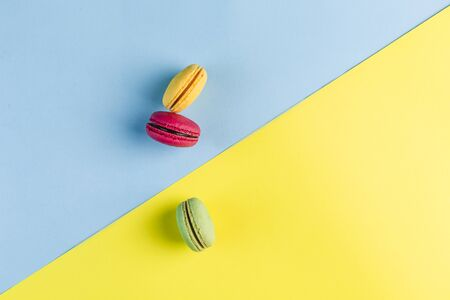 Multicolored macaroons on a blue and yellow background, top view, Flatley with copy space. Dessert with melon, lemon and raspberry flavor. Art