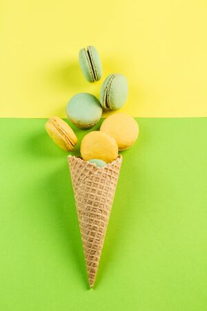 Multicolored macaroons in a waffle cone on a green and yellow background, top view, Flatley with copy space. Dessert with melon, lemon and raspberry flavor. Art 版權商用圖片 - 131408748
