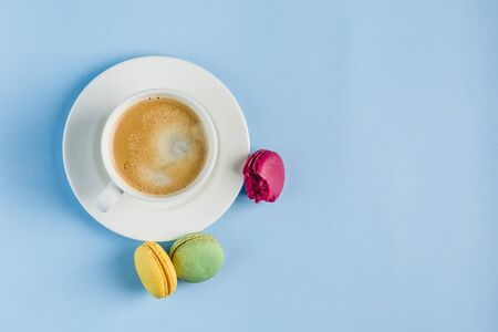 Multicolored macaroons with a white Cup of coffee on a blue background, top view, flat lay with copy space. Dessert with melon, lemon and raspberry flavor. Art 版權商用圖片