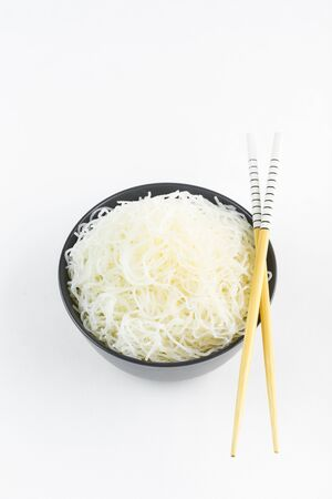 Cellophane rice noodles in a black bowl with chopsticks on white background, isolate, top view. Asian food. Copy space. Stockfoto