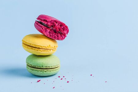 Colorful macaroons on a blue background, close-up, Flatley with copy space. Dessert with melon, lemon and raspberry flavor. Art Stockfoto