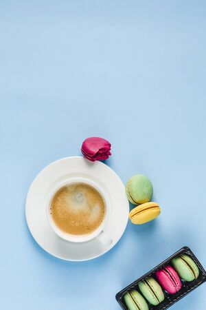 Multicolored macaroons with a white Cup of coffee on a blue background, top view, flat lay with copy space. Dessert with melon, lemon and raspberry flavor. Art 版權商用圖片 - 131409091