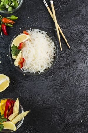 Rice noodles funchosa with vegetables in a black bowl with chopsticks on a dark background, top view, flatlay. Asian food. Copy space.