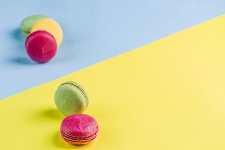 Multicolored macaroons on a blue and yellow background, top view, Flatley with copy space. Dessert with melon, lemon and raspberry flavor. Art 版權商用圖片 - 131408994