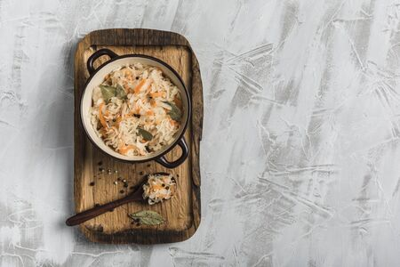 Fermented cabbage in a plate on a wooden tray with a spoon on a light background. Top view. Copyspace. Horizontal orientation. Flat lay. 版權商用圖片