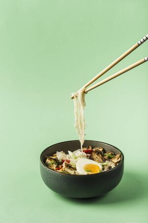 Noodle bowl with mushrooms, egg, tofu cheese and chopsticks on a green background. Asian food concept. Close up with copyspace. Vertical orientation.