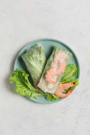Spring rice paper roll with shrimp, avocado, paprika, lettuce and cottage cheese on a bright plate on a white background. Top view with a copy space. Vertical orientation. Фото со стока