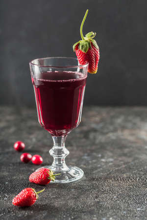 The concept of a summer refreshing drink from red berries: berry Morse of fresh strawberries and cranberries is a great drink to quench your thirst on a black background with a copy space. Vertical orientation.