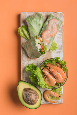 Spring rice paper roll with shrimp, avocado, paprika, lettuce and cottage cheese on a wooden white Board on an orange background. Vegan food. Top view. Vertical orientation. Фото со стока