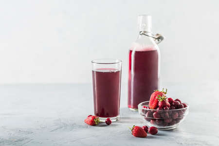 The concept of a summer refreshing drink made from red berries: berry Morse made from fresh strawberries and cranberries is a great drink to quench your thirst on a light background with a copy space. Horizontal orientation. Stock Photo