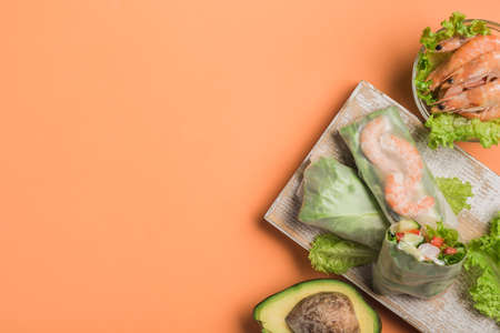Spring rice paper roll with shrimp, avocado, paprika, lettuce and cottage cheese on a wooden white Board on an orange background. Vegan food. Top view with a copy space. Horizontal orientation. Фото со стока