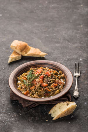 Salad with eggplant and tomatoes in a brown clay plate with a fork for eating and fresh pita bread on a dark background. Side view with a copy of the text space. Vertical orientation. Banque d'images