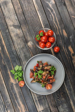 Warm salad with eggplant and tomatoes on a light flat plate and cherry tomatoes on a dark wooden background. Top view with a copy space for the text. Vertical orientation. Flat lay Banque d'images