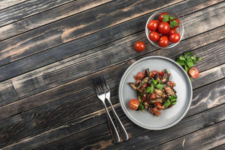 Warm salad with eggplant and tomatoes on a light flat plate with forks for eating and cherry tomatoes on a dark wooden background. Top view with a copy space for the text. Horizontal orientation.