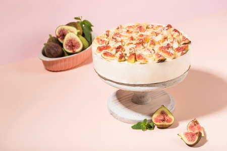 Yogurt cake with figs on a white wooden stand on a light pink background. A delicious dessert for a birthday and holiday. Side view with a copy space for the text. Horizontal orientation.