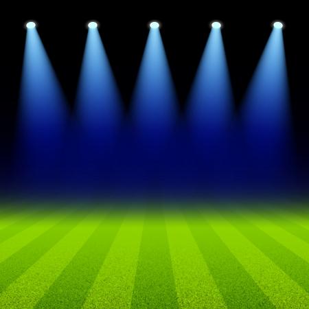 campeonato de futbol: Focos brillantes iluminan el campo de fútbol verde