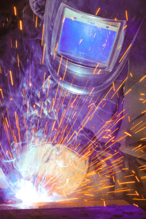 Welder on the production of weld metal. Sparks fly smoke Imagens