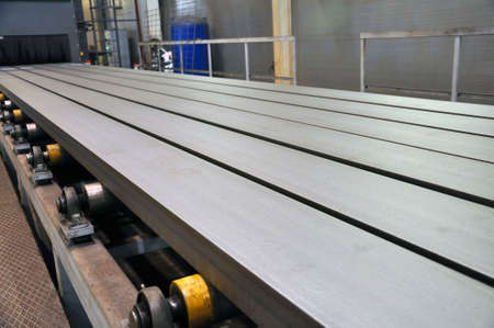 Roller conveyor for the supply of metal products to the installation of sandblasting. Production Stock Photo