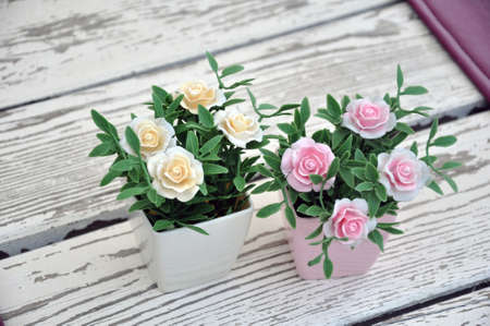 Artificial flowers in pots on the table. Table setting Stockfoto