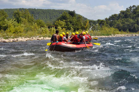 Alanya Turkey - August 18, 2019: Rafting, a group of young people with a guide rafting along a mountain river. Extreme and fun sport at a tourist attraction.